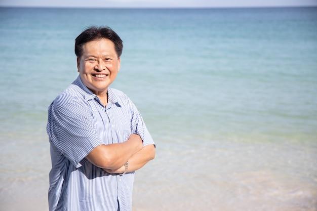 Zelfverzekerde aziatische middelbare leeftijd man met gekruiste armen gebaar