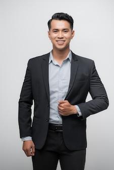 Zelfverzekerde aziatische zakenman glimlachend en kijkend naar de camera