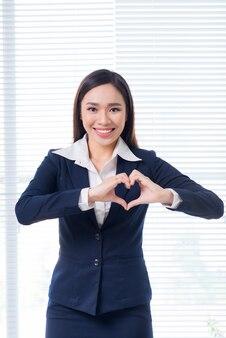 Zelfverzekerde aziatische zakenvrouw gebaar handen maken hartvorm