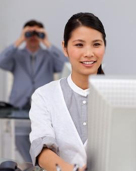 Zelfverzekerde aziatische zakenvrouw op een computer