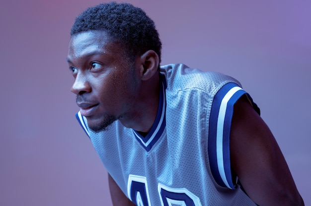 Zelfverzekerde basketbalspeler poseert met bal. professionele mannelijke baller in sportkleding die sportspel speelt, lange sportman