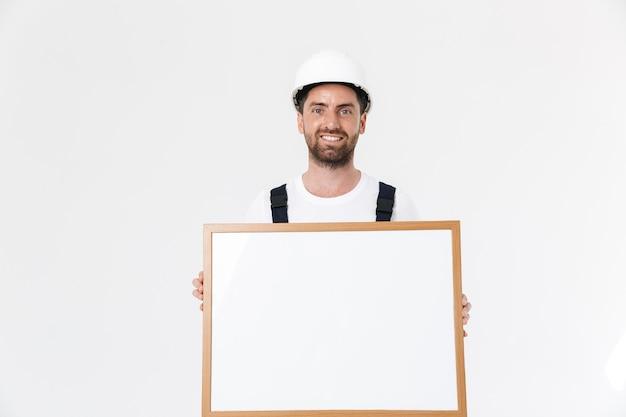 Zelfverzekerde bebaarde bouwman met overall en veiligheidshelm die geïsoleerd over een witte muur staat en een leeg bord toont