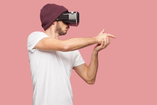Zelfverzekerde bebaarde jonge hipster man in wit overhemd en casual hoed staand, met vr videospelletjes spelend, tonend geweer zingen met vinger zoals schieten. binnen, geïsoleerd, studio-opname, roze achtergrond
