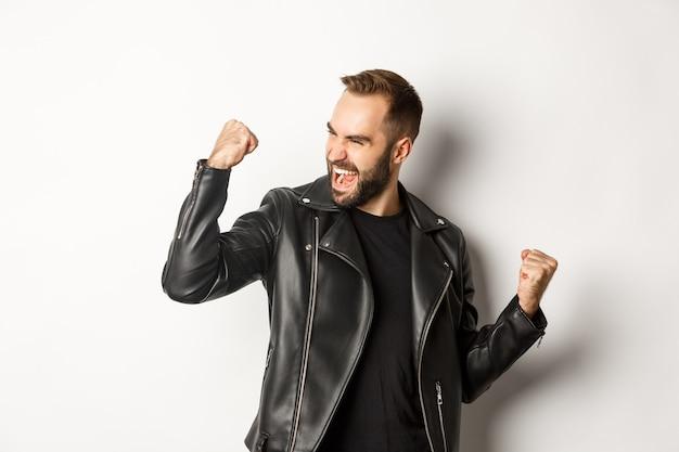Zelfverzekerde bebaarde man die overwinning viert, prijs wint, vuistpomp maakt en zich verheugt, zwart lederen jas draagt