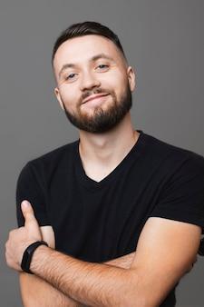 Zelfverzekerde bebaarde man in zwart t-shirt glimlachend en camera kijken terwijl staande op een grijze achtergrond en armen gevouwen