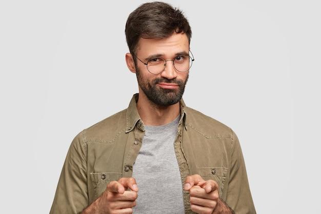 Zelfverzekerde bebaarde man wijst met beide wijsvingers, selecteert iets, heeft donkere stoppels, staat alleen tegen witte muur. aantrekkelijke, zelfverzekerde ushaven-man drukt zijn keuze uit