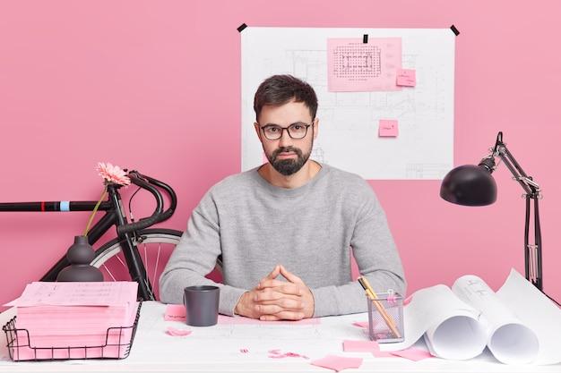 Zelfverzekerde bebaarde professionele mannelijke ingenieur klaar om u te helpen met uw nieuwe huis ontwerpproject poseert op desktop drinkt koffie omringd door blauwdrukken doet papierwerk werkt thuiskantoor