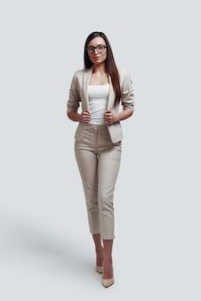 Zelfverzekerde bedrijfsexpert. volledige lengte van aantrekkelijke jonge vrouw die naar de camera kijkt terwijl ze tegen een grijze achtergrond staat
