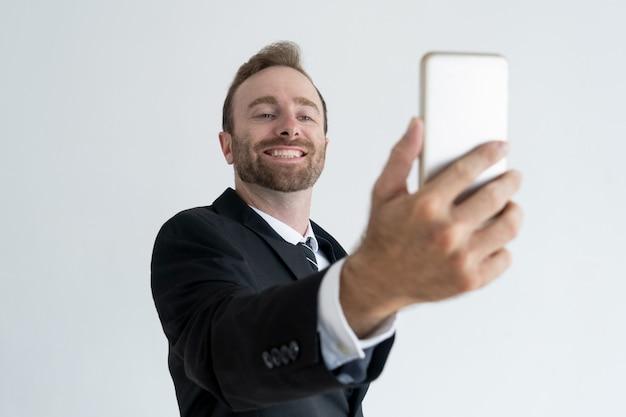 Zelfverzekerde bedrijfsmens die en selfie foto op smartphone stellen nemen.