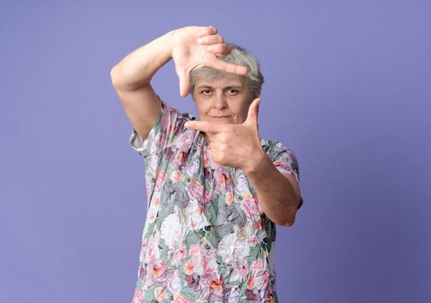 Zelfverzekerde bejaarde gebaren frame handteken geïsoleerd op paarse muur