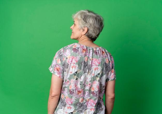 Zelfverzekerde bejaarde tribune die zij, achteraanzicht bekijkt, dat op groene muur wordt geïsoleerd
