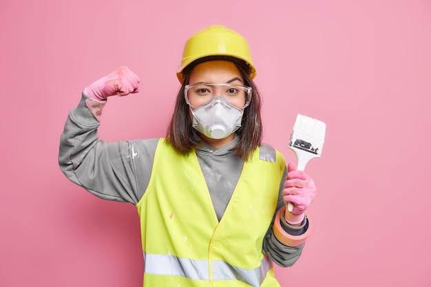 Zelfverzekerde, bekwame vrouwelijke bouwer heft arm op, toont spieren die penseel vasthouden
