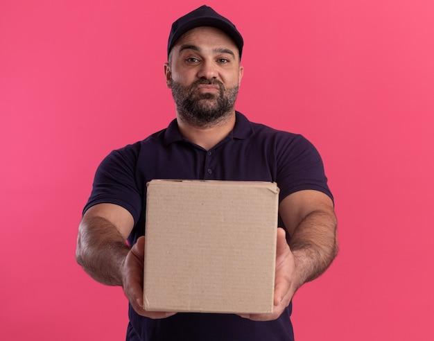 Zelfverzekerde bezorger van middelbare leeftijd in uniform en pet met doos aan de voorkant geïsoleerd op roze muur