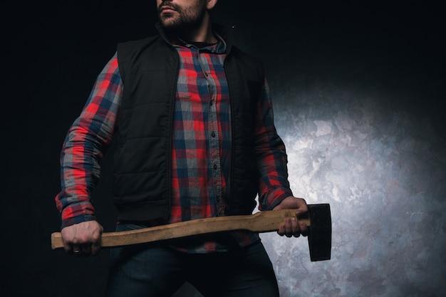 Zelfverzekerde bijl. gewapende man met bijl. gevaarlijke onherkenbare landelijke man op zwarte achtergrond close-up, bescherming concept