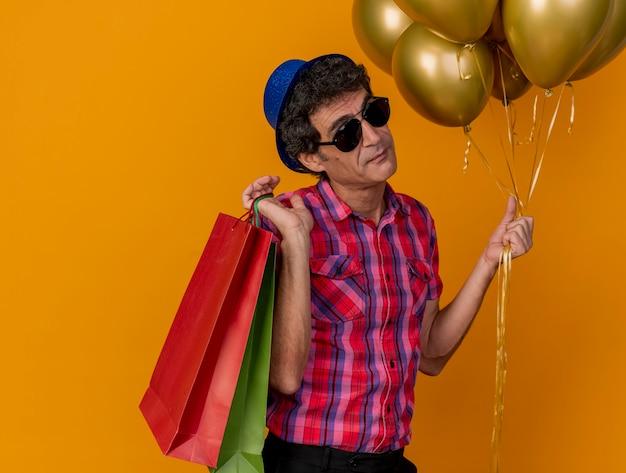 Zelfverzekerde blanke feestmens van middelbare leeftijd met feestmuts en zonnebril met ballonnen en papieren zakken op schouder geïsoleerd op een oranje achtergrond met kopie ruimte