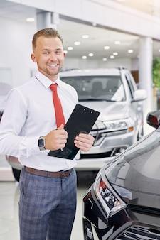 Zelfverzekerde blanke glimlachende autodealer op het werk