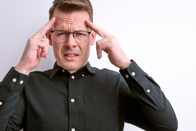 Zelfverzekerde blanke man probeert te onthouden, geconcentreerd op gedachten aanraken van tempels, het dragen van een bril geïsoleerd op een witte muur