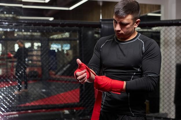 Zelfverzekerde blanke mannelijke kickbokser vechter bereidt zich voor op gevecht, hand in rood verband wikkelen, maak je klaar, ga trainen en oefenen