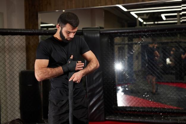 Zelfverzekerde blanke mannelijke kickbokser vechter bereidt zich voor op gevecht, hand in verband wikkelen, maak je klaar, ga trainen en oefenen
