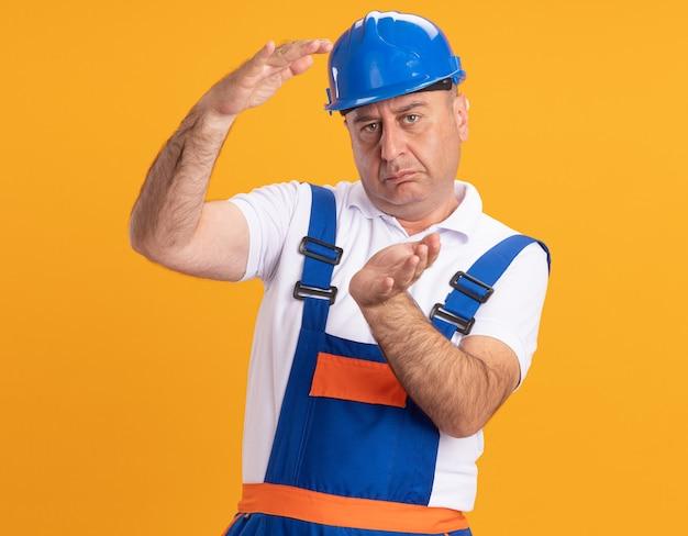Zelfverzekerde blanke volwassen bouwersmens in uniform beweert iets op sinaasappel vast te houden