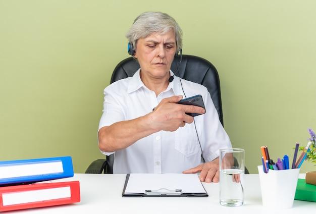 Zelfverzekerde blanke vrouwelijke callcenter-operator op een koptelefoon die aan het bureau zit met kantoorhulpmiddelen die de telefoon vasthouden en bekijken