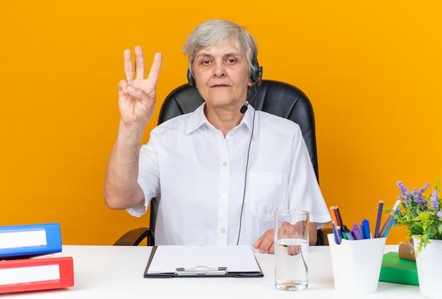 Zelfverzekerde blanke vrouwelijke callcenter-operator op een koptelefoon die aan het bureau zit met kantoorhulpmiddelen die drie met vingers gebaren