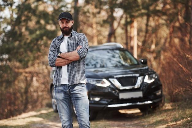 Zelfverzekerde blik. bebaarde man in de buurt van zijn gloednieuwe zwarte auto in het bos. vakanties concept