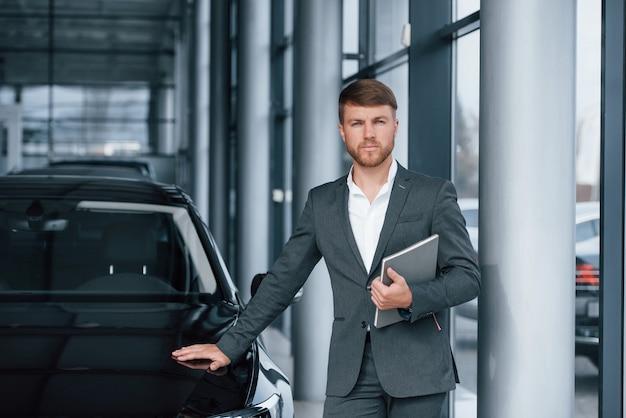 Zelfverzekerde blik. moderne stijlvolle bebaarde zakenman in de auto salon