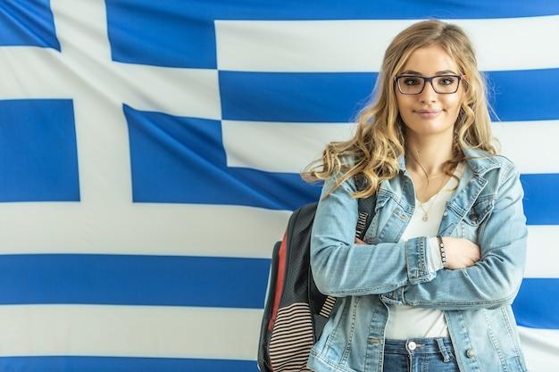 Zelfverzekerde blonde jeugd vrouwelijke student met griekse vlag op de achtergrond.