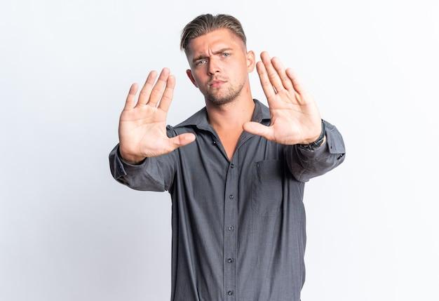 Zelfverzekerde blonde knappe man gebaren stopbord geïsoleerd op een witte muur met kopie ruimte