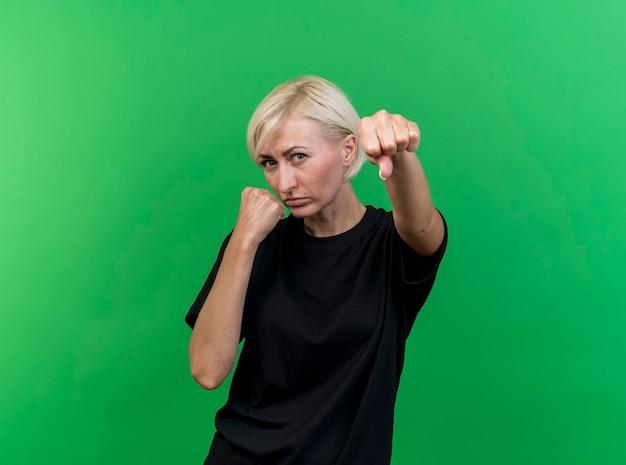 Zelfverzekerde blonde slavische vrouw die van middelbare leeftijd camera bekijkt die boksgebaar doet dat op groene achtergrond met exemplaarruimte wordt geïsoleerd