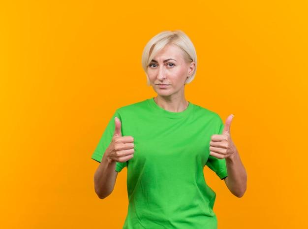 Zelfverzekerde blonde slavische vrouw op middelbare leeftijd die voorzijde bekijkt die duimen toont die omhoog op gele muur met exemplaarruimte wordt geïsoleerd