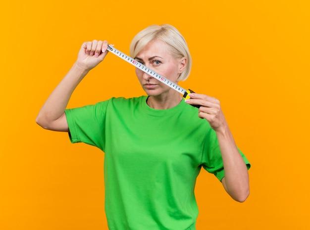 Zelfverzekerde blonde slavische vrouw van middelbare leeftijd die de bandmeter van de cameraholding voor gezicht bekijken dat op gele achtergrond wordt geïsoleerd