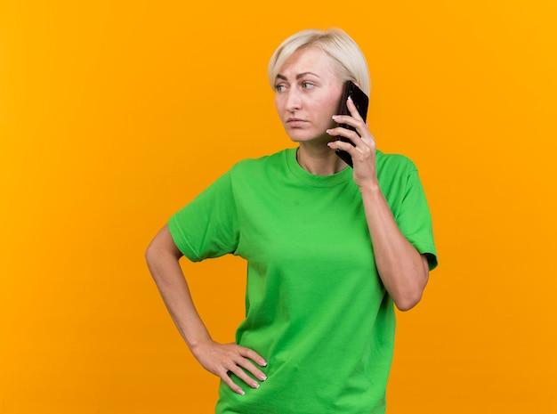 Zelfverzekerde blonde slavische vrouw van middelbare leeftijd die op telefoon spreekt die hand op taille houdt die kant bekijkt die op gele muur met exemplaarruimte wordt geïsoleerd