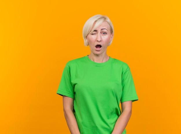Zelfverzekerde blonde slavische vrouw van middelbare leeftijd die voorzijde bekijkt en knipoogt geïsoleerd op gele muur met exemplaarruimte