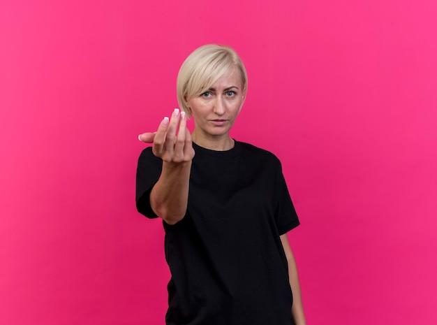 Zelfverzekerde blonde slavische vrouw van middelbare leeftijd doen kom hier gebaar geïsoleerd op karmozijnrode muur met kopie ruimte