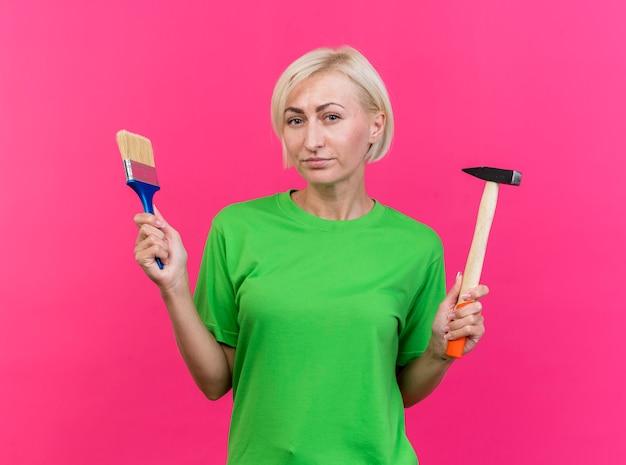 Zelfverzekerde blonde slavische vrouw van middelbare leeftijd kijken naar de verfborstel en de hamer van de cameraholding die op karmozijnrode achtergrond wordt geïsoleerd