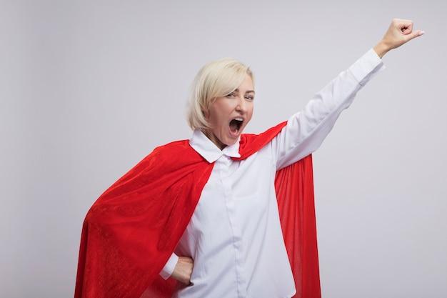 Zelfverzekerde blonde superheld vrouw van middelbare leeftijd in rode cape doet superman gebaar schreeuwen