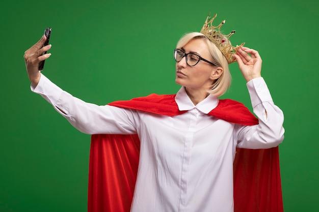 Zelfverzekerde blonde superheld vrouw van middelbare leeftijd in rode cape dragen van een bril en kroon grijpen kroon nemen selfie geïsoleerd op groene muur