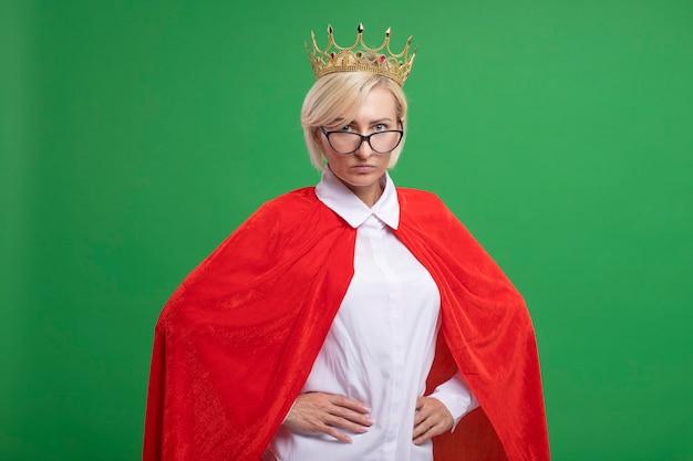 Zelfverzekerde blonde superheld vrouw van middelbare leeftijd in rode cape met een bril en kroon die de handen op de taille houdt en naar de voorkant kijkt geïsoleerd op de groene muur met kopieerruimte