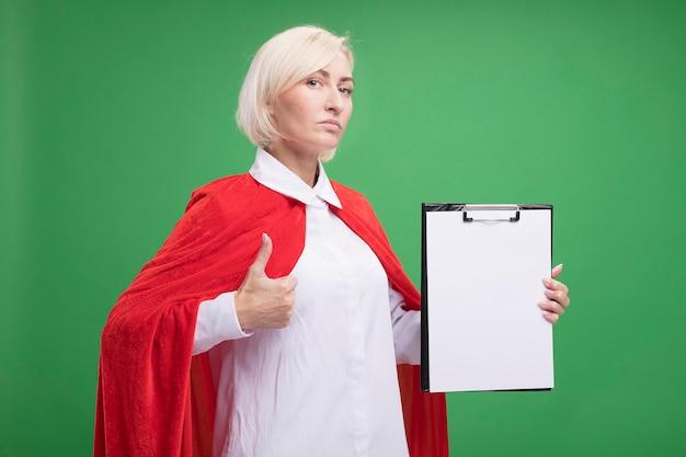 Zelfverzekerde blonde superheld vrouw van middelbare leeftijd in rode cape met klembord naar voren kijkend naar de voorkant met duim omhoog geïsoleerd op groene muur