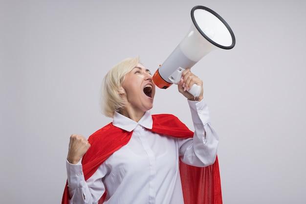 Zelfverzekerde blonde superheldenvrouw van middelbare leeftijd in een rode cape die in een luidspreker schreeuwt en met gebalde vuist opkijkt