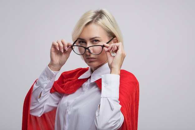 Zelfverzekerde blonde superheldenvrouw van middelbare leeftijd in rode cape die een bril draagt en grijpt die naar de voorkant kijkt geïsoleerd op een witte muur met kopieerruimte