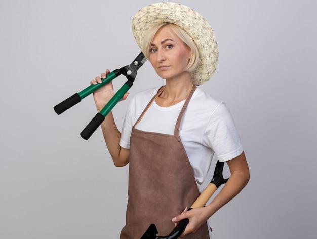 Zelfverzekerde blonde tuinmanvrouw van middelbare leeftijd in uniform met hoed