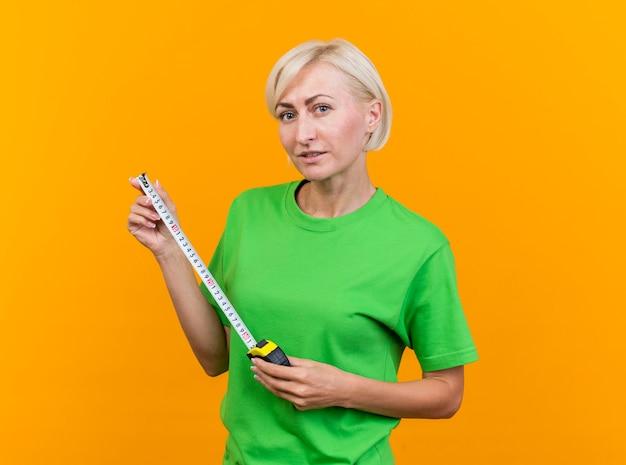 Zelfverzekerde blonde vrouw op middelbare leeftijd die de meter van de de holdingsband aan de voorkant bekijkt die op gele muur wordt geïsoleerd