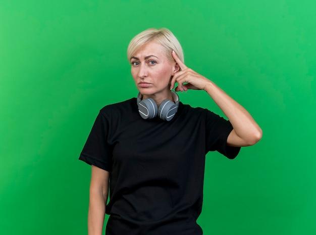Zelfverzekerde blonde vrouw van middelbare leeftijd die een koptelefoon op de nek draagt en naar de voorkant kijkt, denkt gebaar dat op groene muur wordt geïsoleerd