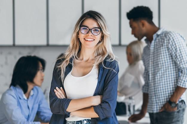 Zelfverzekerde blonde vrouwelijke manager poseren met glimlach na conferentie met andere werknemers. aziatische programmeur in gesprek met afrikaanse freelancer terwijl blonde secretaresse lachen.