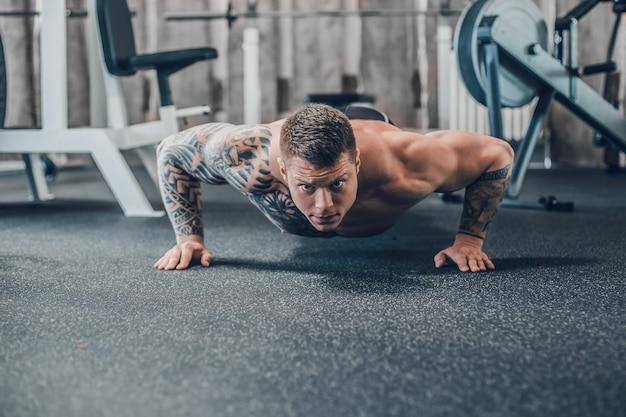 Zelfverzekerde bodybuilder maakt push-ups in de fitnessruimte. foto met kopieerruimte