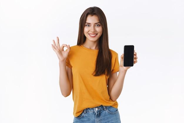 Zelfverzekerde, brutale en ontspannen knappe vrouw in geel t-shirt, smartphone vasthoudend, display of mobiel scherm tonend met tevreden uitdrukking, maak goed teken in goedkeuring, witte achtergrond