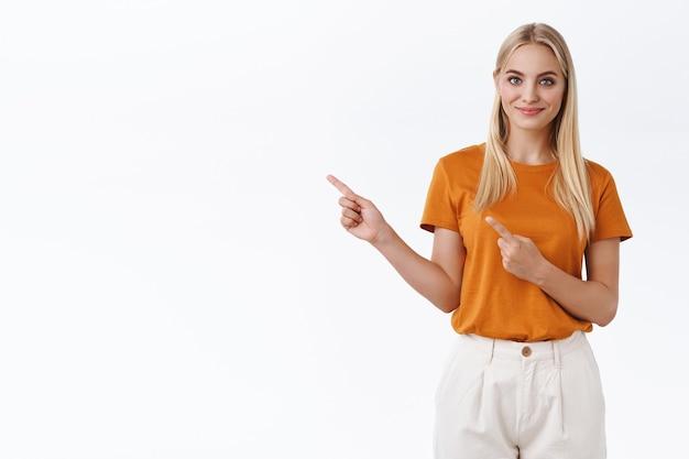 Zelfverzekerde, brutale knappe moderne blonde vrouw in oranje t-shirt, broek, wijzende vingers naar links en glimlachend zelfverzekerd, aanmoedigen om een goede keuze te maken, advies geven, promo voorstellen, witte achtergrond